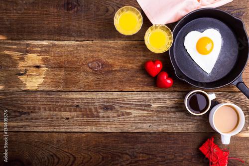 Heart shape fried egg, fresh orange juice and coffee. Top view