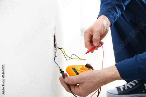 Photo Electrician measuring earth resistance prior to installation of new socket, clos
