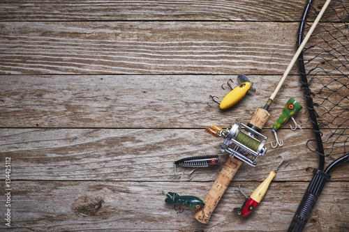 Fotobehang Vissen antique fishing lures, rod, and reel on a wood table