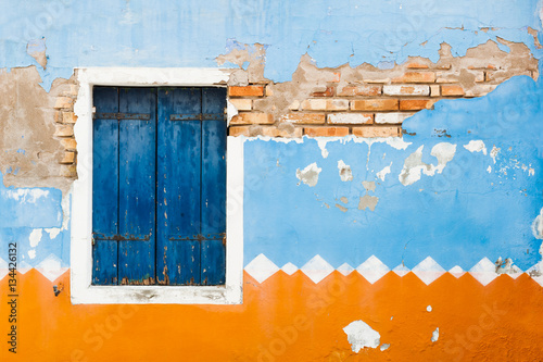 Ancient wall of the house and window with blue shutters. Canvas