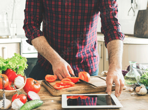 Poster Cuisine Man following recipe on tablet and cooking healthy food