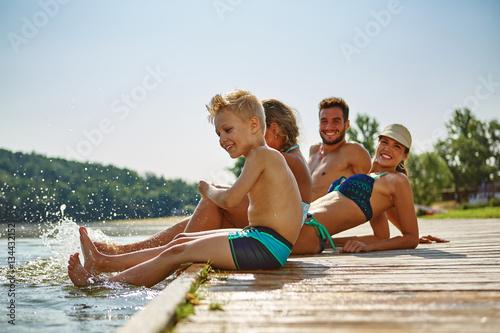Photo  Familie plantscht mit Füßen im Wasser