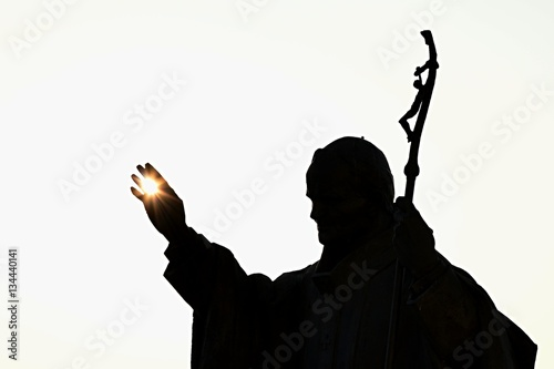 Obraz Silhouette of statue of pope John Paul The Second with afternoon sun in his palm, castle Nitra, Slovakia - fototapety do salonu