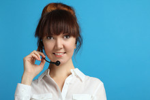 Portrait Of A Young Smiling Woman With Headset Working In A Call Center.