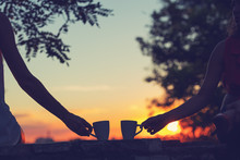 Friends Drinking Coffee In Sunset / Sunrise. Shallow Depth Of Field.