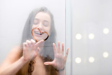 Young Woman Drawing Heart Shape On The Glass In The Shower