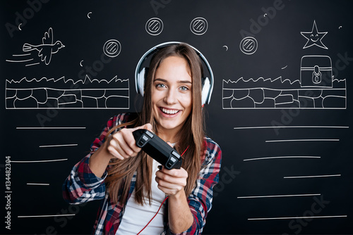 Fotografering  Cheerful delighted young woman playing video games