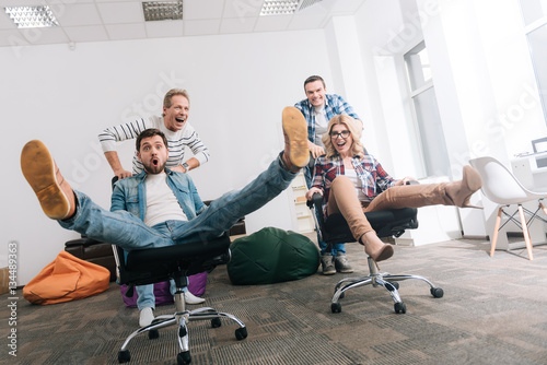 Joyful happy people riding in the office chairs