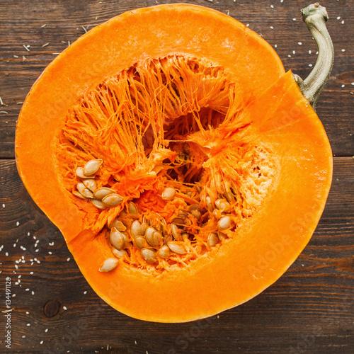 Round orange pumpkin half in cut. Close-up of fresh squash cutaway, ready for preparing. Seasonal fruit, healthy eating, nutrition concept
