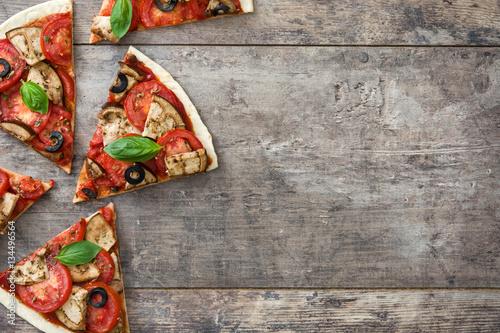 Fotografia vegetarian pizza slice with eggplant, tomato, black olives, oregano and basil on wooden background