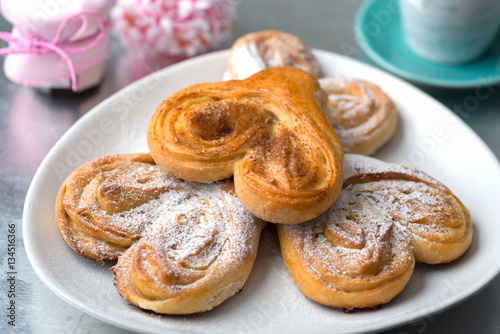 Foto op Plexiglas Bakkerij Buns in the form of heart with cinnamon and powdered sugar with
