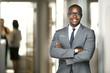 Leinwandbild Motiv Handsome cheerful african american executive business man at the workspace office