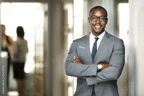Handsome cheerful african american executive business man at the workspace offic Wallpaper Mural