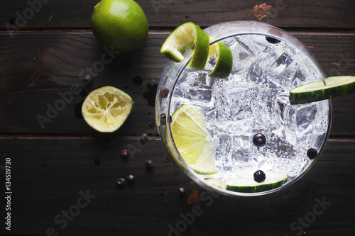 Glass of gin tonic with ice, cucumber, lime over a dark wood table