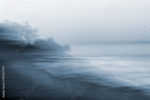 Motion Blurred Seascape. A monotone, blurred seascape made using a long exposure combined with horizontal panning motion.