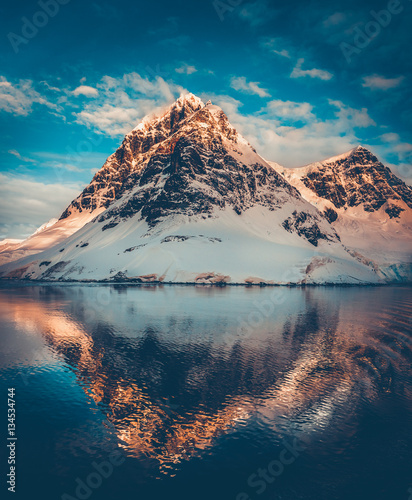 Foto op Canvas Antarctica Antarctic landscape with snow covered mountains reflected in ocean water. Sunset warm light on the mountain peak, blue cloudy sky in the background. Beautiful nature landscape. Travel background.