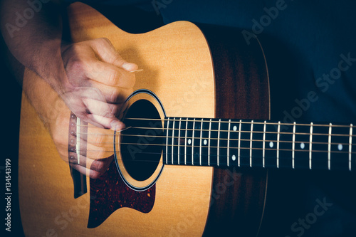 Musician's hand is strumming a yellow acoustic guitar Fototapeta
