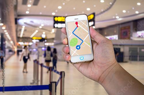 Fotografia  Mężczyzna trzyma telefon komórkowy z nawigacją GPS mapy.