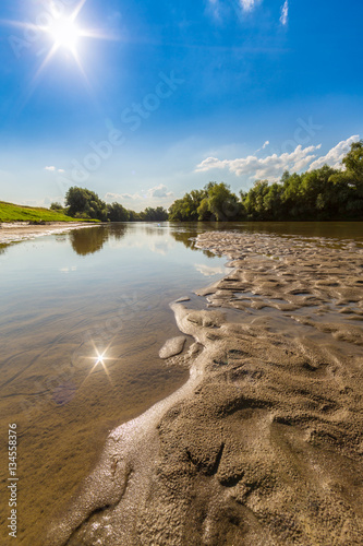 Poster Reflexion Bright sun over wild river, on a beautiful summer day