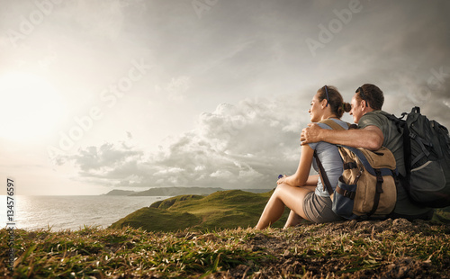 Photo  Couple tourists with backpacks enjoying sunset on top of a mountain