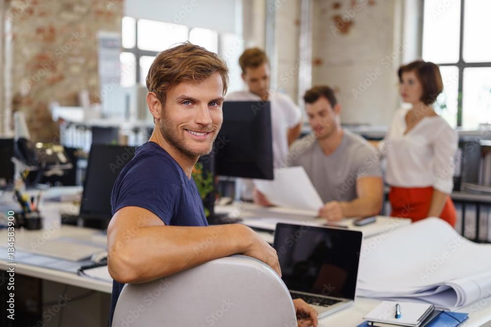Fototapety, obrazy: lächelnder mann im büro mit kollegen im hintergrund