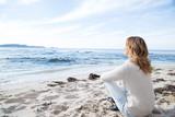 Fototapeta See - femme en hiver assise sur la plage