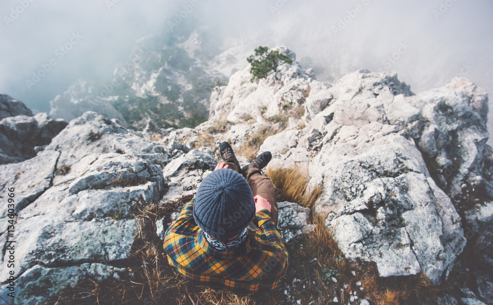 Fototapety, obrazy: Traveler man relaxing alone on rocky mountain summit over clouds Travel Lifestyle success concept adventure active vacations outdoor top view