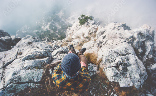 Fotografia  Traveler man relaxing alone on rocky mountain summit over clouds Travel Lifestyl