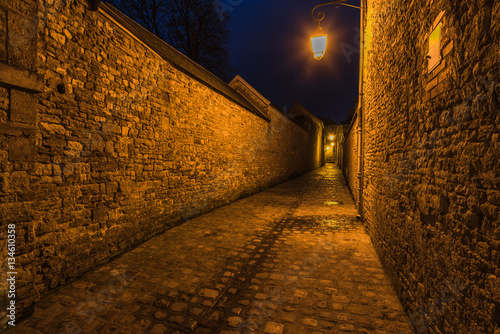 Fototapeten Schmale Gasse Old french mediewal cobbled street in Carentan,France