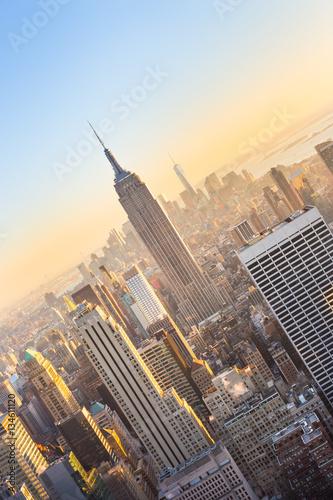 Plakat Nowy Jork. Panoramę centrum Manhattanu z oświetlonym Empire State Building i drapaczami chmur o zachodzie słońca widzianym z tarasu widokowego Top of the Rock. Kompozycja pionowa.