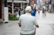 Starszy mężczyzna z czapce jadący ulicą na rowerze