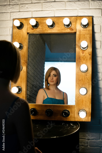 Photo  beautiful girl looking through the mirror in dressing room