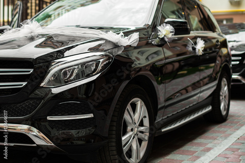 Fototapeta  Black Mercedes G-Class decorated with white bows and flowers for