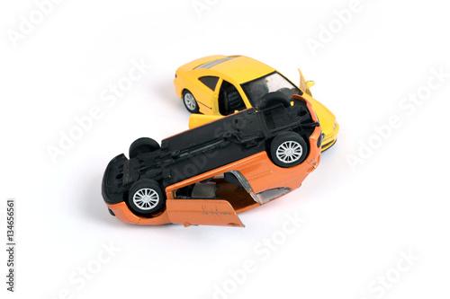 Fotografie, Obraz  Wypadek samochodowy. Kolizja dwóch pojazdów. Dziecięce zabawki.