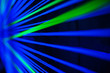 canvas print picture - Black abstract background with blurred glowing blue and green thread or lines. Selective focus