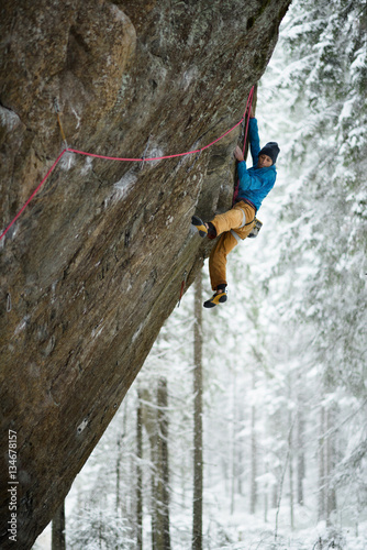 Papiers peints Glisse hiver Extreme winter sport. Young man climbing a rock with belay. Rope climbing.