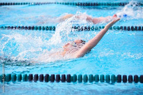 Motion blur image of a boy swimming backstroke in a race. Wallpaper Mural