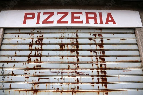 Poster Pizzeria the big sign of Pizzeria with the gate closed
