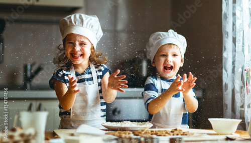 Photo happy family funny kids bake cookies in kitchen