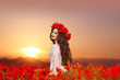Beautiful girl in poppies field at sunset. Happy smiling teen po
