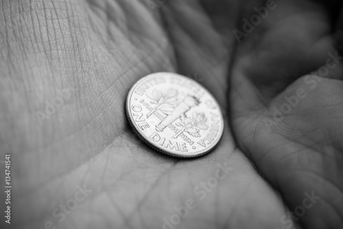 Fotografía  Coin on a palm of a hand - focus on One dime