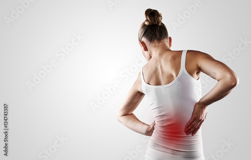 Fotografía  Portrait of young woman touching her painful back over grey background with copy space
