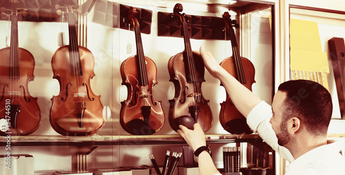Spoed Foto op Canvas Muziekwinkel Positive man purchasing traditional violins in store
