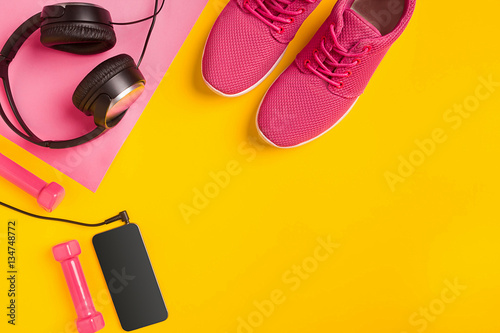 Fitness accessories on a yellow background. Sneakers, bottle of water, earphones and dumbbells.