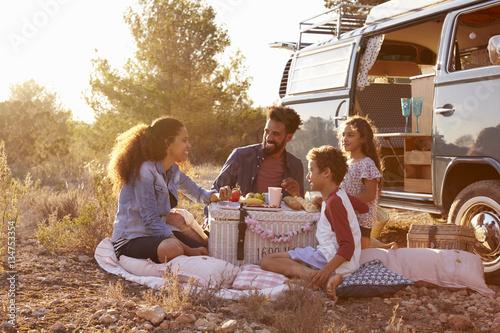In de dag Kamperen Family having a picnic beside their camper van, full length