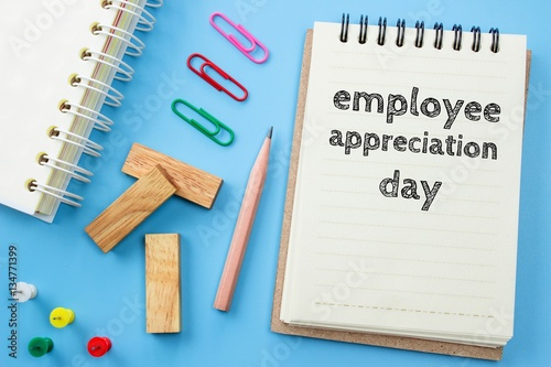 Photo  Text Employee appreciation day on white paper book and office supplies on blue d