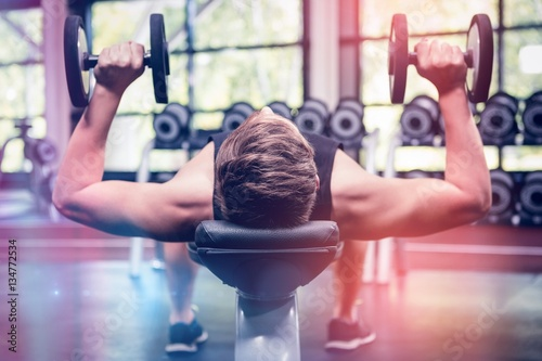 Obraz Man lifting dumbbell weights while lying down - fototapety do salonu