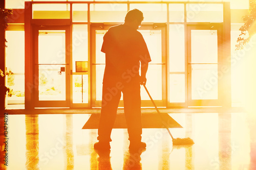 Photo Janitor mopping in an office