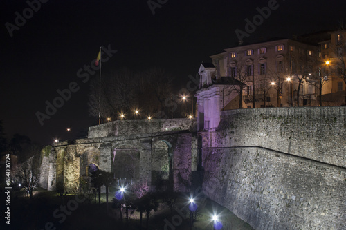 Poster Artistique Bergamo - Old city (Citta Alta). One of the beautiful city in Italy. Lombardia. Landscape on the old gate named Porta San Giacomo during the night illuminated pink color. Venetian walls of Bergamo.