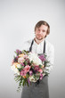 beautiful bouquet made of different flowers in young man hand . colorful color mix flower. Work clothing in a white shirt and gray apron